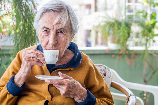 Old woman sitting and drinking Turkish coffee in the balcony on a sunny day.