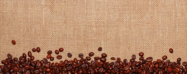 Panorama lined with coffee beans on the background of sack cloth