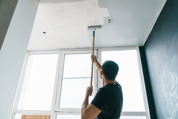 the man paints the walls and the ceiling in gray color, standing with his back to the camera. Focus on the roller. Painting and repair of the room.