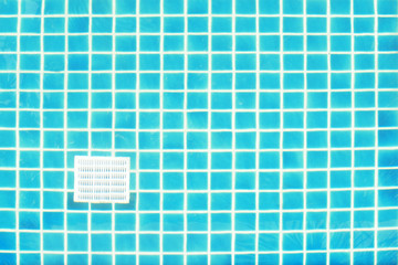 Blue tile square mosaic and drainage at the pool floor. Background and texture of blue tile square mosaic. Take photo through the water.