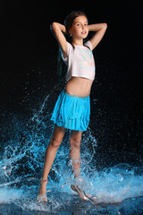 Charming slender child standing at full body on tiptoe. Pretty young beautiful girl with bare legs in wet clothes and skirt. Attractive yound teenager in splashes of water.
