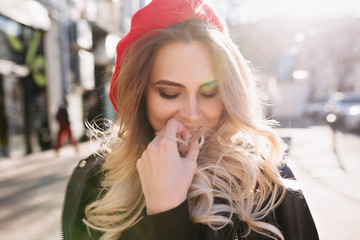 Close-up portrait of sensitive pretty young woman with wavy long hair dressed red hat closed eyes and smiles. True emotions.