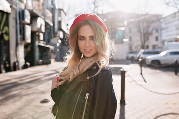 Stylish lovely girl with long blond hair dressed leather jacket and red hat walking on the street with lovely smile in sunlight