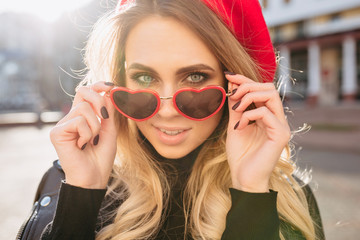 Close-up portrait of attractive blond female model dressed red hat and stylish glasses in sunlight. Photo of happy caucasian girl in sunglasses posing outside.