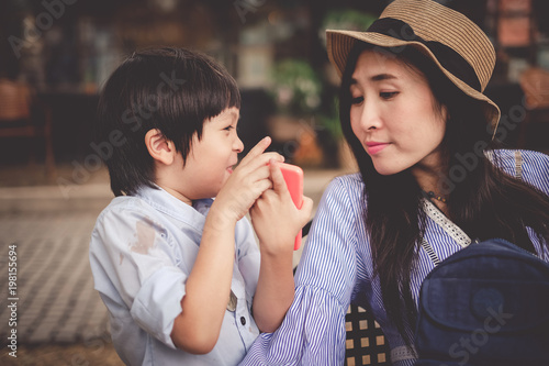 mother and son looking at the picture in mobile phone by fun