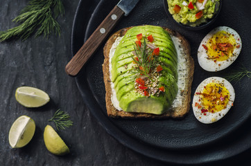 Wholegrain Toast with avocado and creamy cheese,and boiled egg,serves with fresh lemon and on dark plate. Top view with close-up.