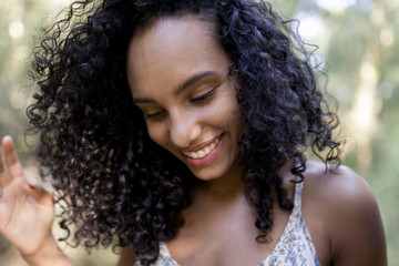 portrait outdoors of a beautiful young afro american woman smiling at sunset. Green background. Lifestyle