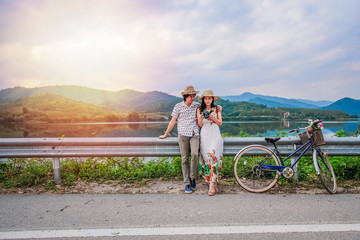 couple traveler standing beside bicycle near the lake background is mountain on vacation.Asia tourists have romance time and enjoying for holiday.