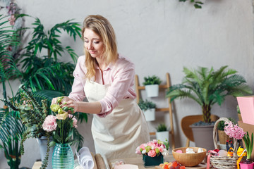Photo of florist woman in apron with flowers in vase at table with marshmallows, marmalade