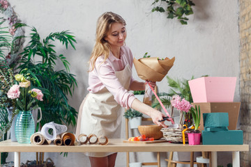 Image of blonde florist in apron with bouquet at table with paper, marmalade, boxes