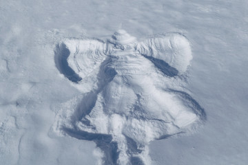 On the white snow the imprint of a child in the form of an angel flapping its wings. Angel's visible head, wings, dress, leg. Rrelief print. Sunny day. Pure snow. Winter vacation on vacation, holidays
