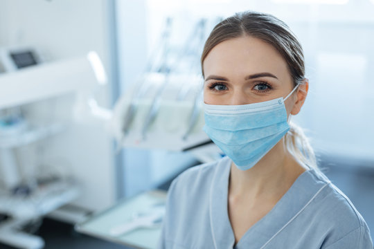 Love my work. Cheerful pretty young female dentist posing for the camera in her office and smiling while wearing a face mask