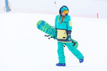 Beautiful young snowboarder girl holding snowboard.
