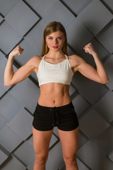 A beautiful athletic girl shows biceps