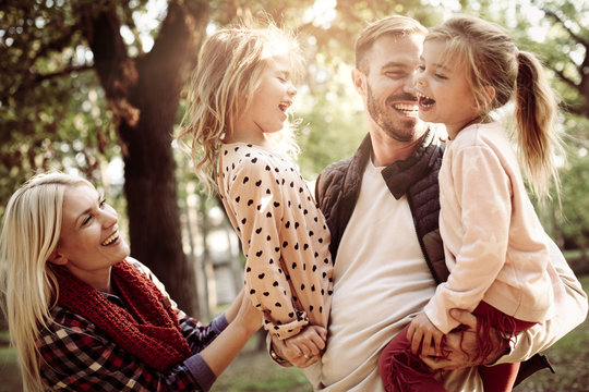 Cheerful family together in park enjoying in nature.