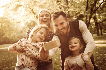 Smiling father taking self portrait of his family in park.