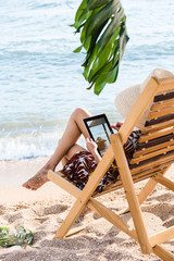 woman with tablet rests in chaise longue on the beach