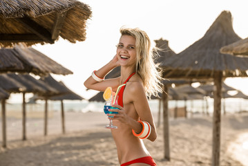 sensual woman in bikini on the beach drinks cocktail