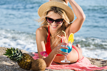 woman on the beach drinks coktail