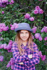 Photo of an attractive beautiful young model girl in colorful shirt with long hair in summer lilac garden