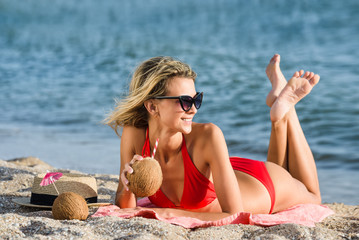 blonde woman in red swimsuit lays on the sand  on the beach and drinks cocktail coconut