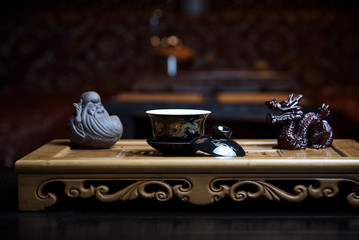 Beautiful dishes for a tea ceremony close-up on a wooden board with statues on the background of a blurred living room.