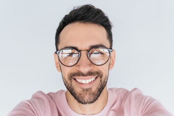 Closeup portrait of handsome young happy smiling bearded male model look at the camera, wears round trendy glasses with toothy smile. Cheerful man in spectacles, pink clothes advertises in studio wall