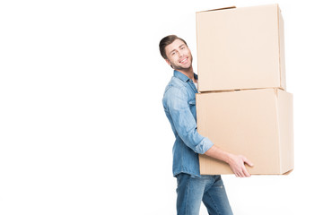 happy young man relocating with cardboard boxes, isolated on white