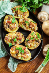 Baked potatoes in jacket stuffed with bacon, mushrooms and chees