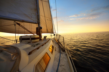 View from the deck of a sail yacht tilted in a wind on a sunset.