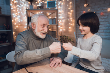 Grandfather and grandson are playing rock paper scissors at night at home.