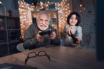 Grandfather and grandson are playing video games at night at home.