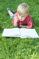 Child boy reading book, lying down on green grass. Blank pages for your content