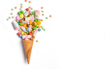 Ice cream cone flat lay image with colorful candy packing into the cone.