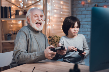 Grandfather and grandson are playing video games on computer at night at home.