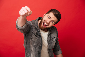 Joyous cheerful man 30s in jeans jacket smiling and pointing index finger on camera, isolated over red background