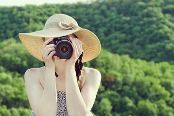 Girl in hat takes pictures against the background of green forest. Front view