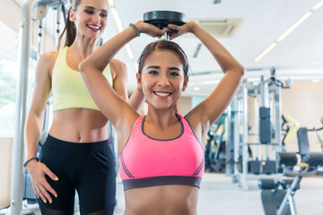 Portrait of a cheerful Indonesian young woman exercising triceps extension with dumbbell during workout under the guidance of her personal trainer