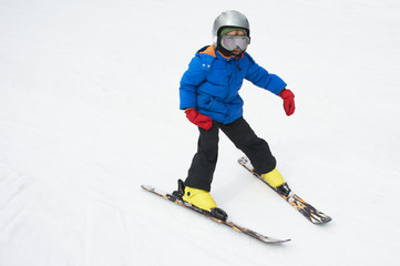 Child boy skiing in the mountains on snowy winter day. Kids in winter sport school in resort. Family fun in the snow. Skier learning and exercising on a slope.