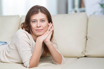 Beautiful adult woman at home on the couch alone on the window