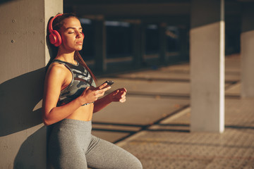 Young woman resting and listen to music after jogging