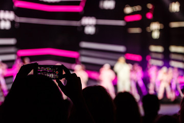 A smartphone held with two hand in order to shoot a footage during a concert.