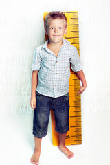 The school boy with huge yellow ruler on the white background. Isolated.