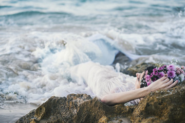 Beautiful mermaid having rest on rocks in wavy sea. Fantasy and myth. Woman in white dress lying in the sea.