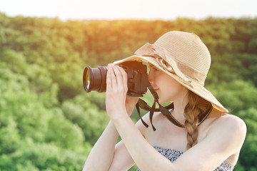 Girl in hat takes pictures against the background of green forest. Side view