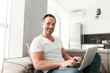 Smiling mature man using laptop computer