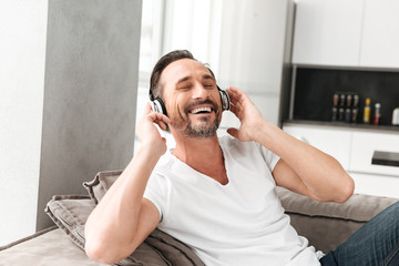 Smiling mature man listening to music with headphones