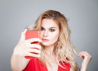 Young beautiful woman making selfie photo on smartphone. Fashion model girl with cell phone