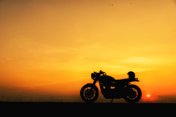 Silhouette of motorcycle parking with sunset background in Thailand,Young Traveller man place helmet on motorbike.Trip of Motorcycle Concept.