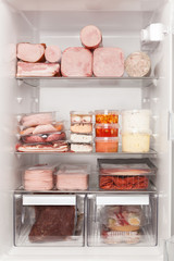 Full fridge of meat and ham. Unhealthy eating concept.
